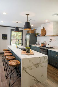 A stylish kitchen with a large marble waterfall island and wooden bar stools