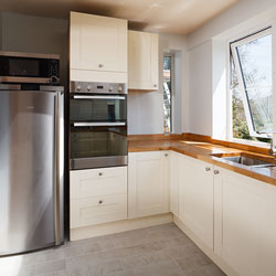 A cream and wood kitchen with stainless steel appliances