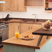 Light timber worktops help to reflect much-needed natural light in open plan kitchen designs.