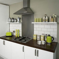 A neutral kitchen with dark wooden worktop and lime coloured accessories