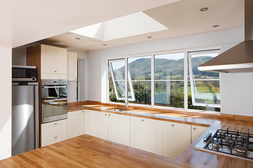 Minimalistic oak kitchen with large windows.