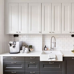 A modern kitchen with black base cabinets and white wall cabinets