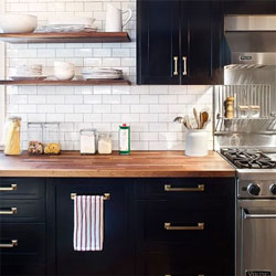 A modern kitchen with black cabinets, gold hardware and a wooden worktop