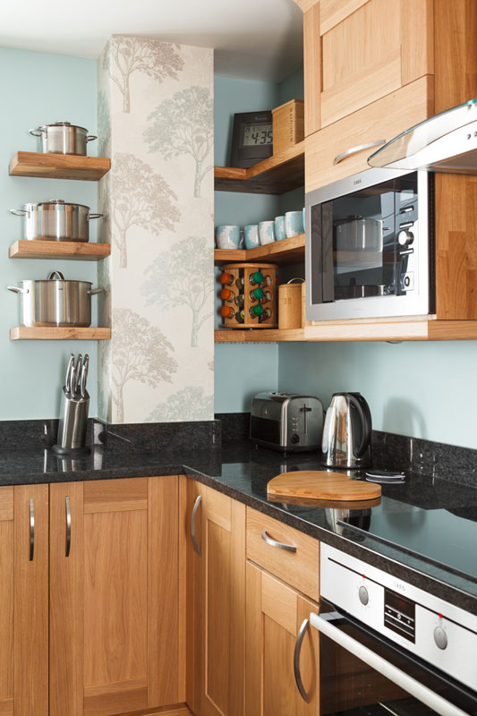 A Modern Kitchen With Floating Shelves And Cabinetry