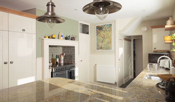 A traditional kitchen with a marble worktop, pendant lamps and white cabinets