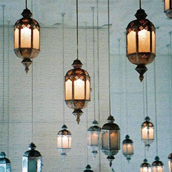 Many Moroccan-style pendant lamps hanging from a ceiling