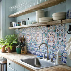 A light-coloured wooden kitchen with Moroccan tiles and a feature wall