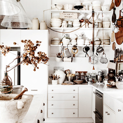 A mostly white kitchen with many neutral coloured accessories