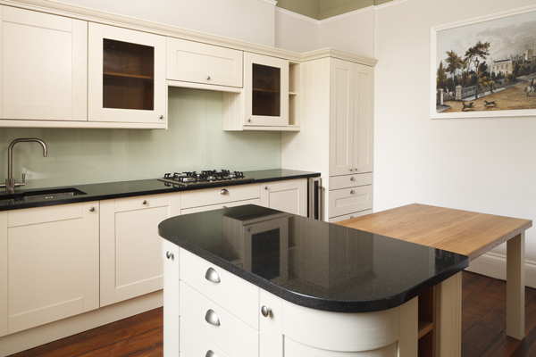 This kitchen contrasts the natural grain of wood against the high gloss work surfaces and glass splashbacks.