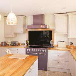 A kitchen with neutral tones, gold pendant lights and a purple oven