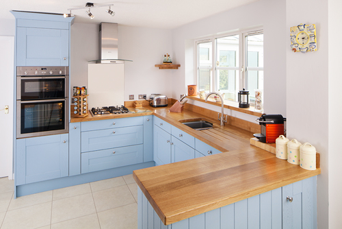An oak kitchen with Shaker frontals painted in Lulworth Blue with solid oak worktop.