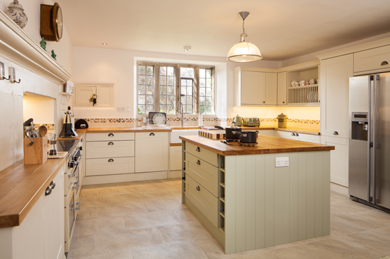 Here, gorgeous oak worktops are paired with cabinet frontals in Farrow & Ball's Clunch and Vert De Terre.