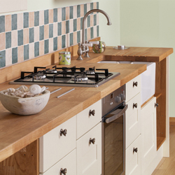 Deluxe prime oak worktops with solid oak kitchen cabinets painted in New White.