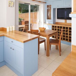 An open-plan kitchen diner with garden views and pale blue cabinets