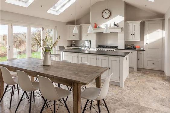 This open plan kitchen diner makes the most of the light coming in from the patio doors and skylights, creating a bright, airy space