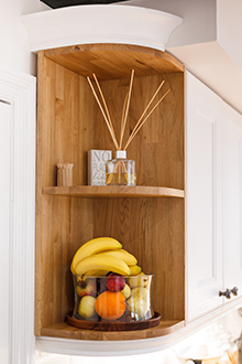 An open curved corner wall cabinet is the perfect place for a fruit bowl in oak kitchens