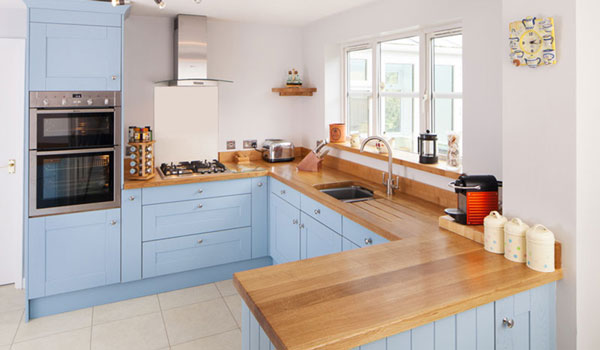 A pale blue oak kitchen with a wooden worktop and stainless steel appliances