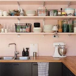 Pale pink walls contrast with a wooden kitchen worktop and dark cabinets.