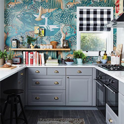 Neutral grey cabinets and a white worktop contrast with a vivid wallpaper with natural themes.