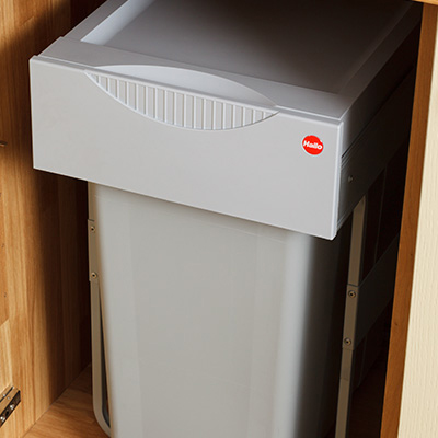 Waste bin within cupboard