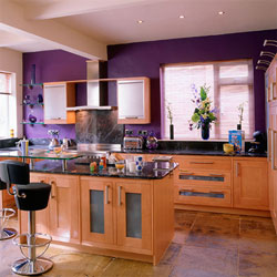 A modern kitchen with wooden cabinets and a purple feature wall