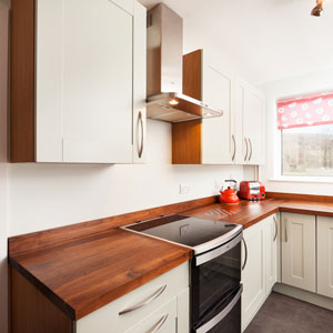 The red accessories in this kitchen break up the white space and could be easily interchanged for a different hue when trends change