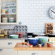 Retro cookware and white subway tiles are well-suited to this vintage-style kitchen solid wood kitchens.