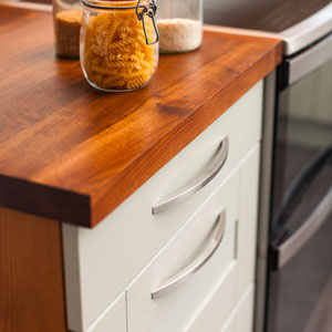 White cabinets are topped with a solid wood worktop. The cabinets have bow handles on.