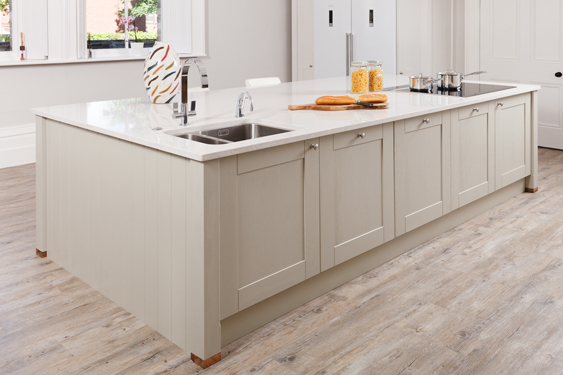 Modern Shaker cabinets and a large white quartz worktop create a kitchen island that provides ample additional work space.