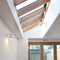 A huge skylight lets a lot of light into a dining area with a solid wood table and chairs.