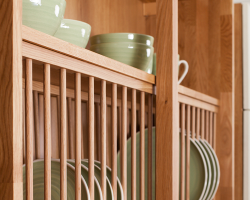 Solid oak plate rack with plates in and a shelf above for bowls.