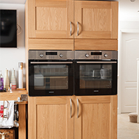 Solid oak Shaker lacquered full-height cabinets with twin single ovens
