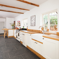 A one-wall traditional kitchen with full stave oak worktops and cabinets painted in Farrow & Ball's Wimborne White