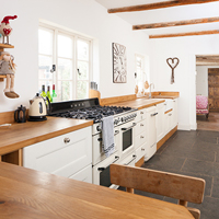 Oak cabinets and worktops alongside retro appliances in a country kitchen