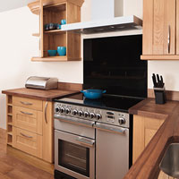 A stainless steel oven alongside our solid wood cabinets and worktops