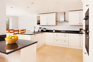 Painted white kitchen with black worktops and stone floor tiles.
