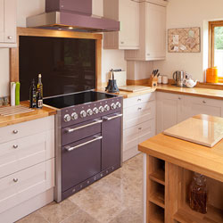 A statement purple oven and extractor fan in an otherwise neutral kitchen with white cabinetry and wooden worktops