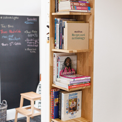 An oak bookshelf with books laid out haphazardly. There is a chalkboard and wooden stool in the background