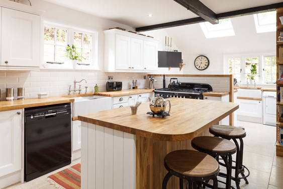 Oak worktops are teamed with white cabinets and end panels in this beautiful solid wood kitchen.