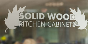 Solid Wood Kitchen Cabinets logo on a glass door