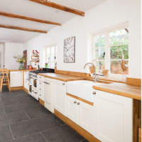 A solid wood worktop on top of white cabinets. Wooden ceiling beams bring character.