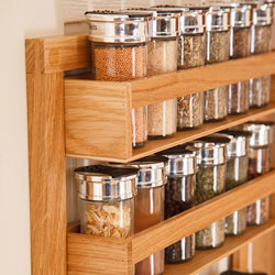 A wooden spice rack with full spice jars