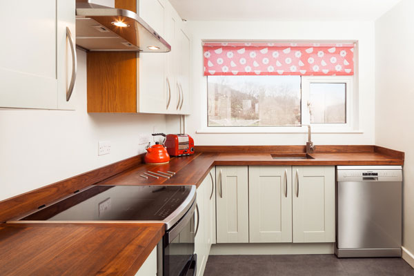 A neutral kitchen with stainless steel appliances and a red patterned window blind