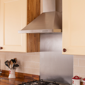Stainless steel splashbacks bounce light back into solid wood kitchens.