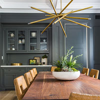 A traditional dining room with grey walls and a wooden table is offset by an ultra-modern gold chandelier-type light.