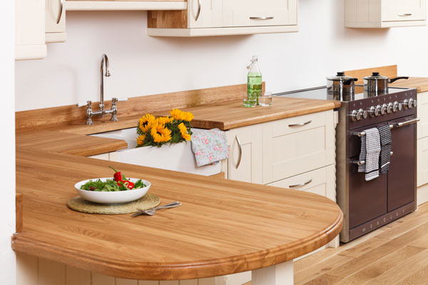 A traditional wood kitchen with a bowl of salad on the worktop
