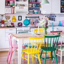 A vibrant kitchen with bright coloured chairs and accessories