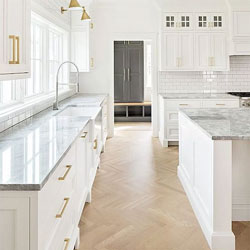 A clean white kitchen with a wooden herringbone floor, a marble worktop and gold handles
