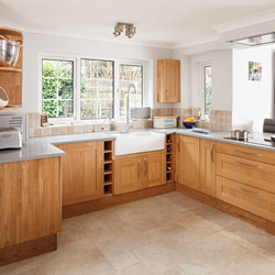 A spacious wooden kitchen with white worktop, Belfast sink and breakfast bar