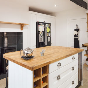 The wood burning stove in this white wood kitchen gives it a strong country style, which is further enhanced by the natural timber used to create work surfaces and open shelving